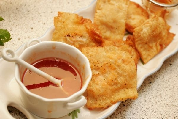 crab rangoons with sweet and sour dip on the side
